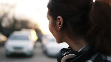 брюнет : Side view of a girl with headphones around her neck. She smiles, turns to look in a blurred perspective. Long brown haired