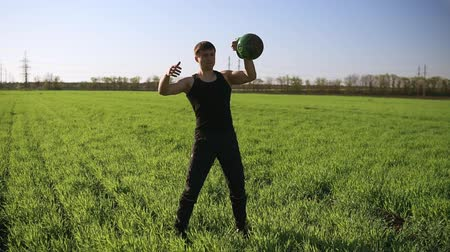 construção muscular : A young man with a sporty physique lifts a weight with one hand. Beautiful nature, standing on a green meadow Vídeos