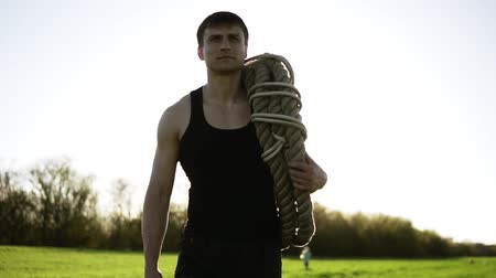 squat : A handsome man, an athlete carries coiled battle ropes on his shoulder after training in the park. Crossfit. Sunny background