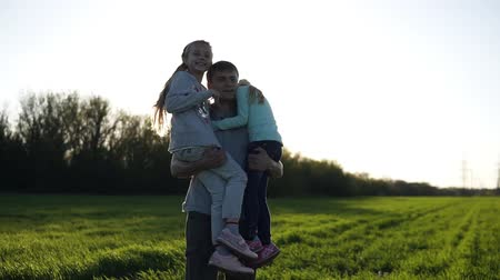 гордый : Proud father of two girls in nature. He carries them in his arms, the sun is shining, the youngest girl sends air kisses. Beautiful field with green grass. Slow motion