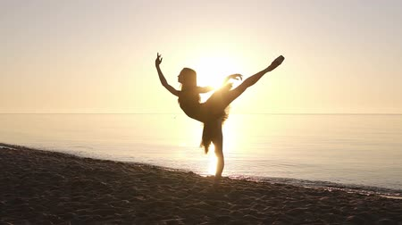 tüt : Silhouette of an elegant ballerina in a tutu in the rays of the morning sun. Doing exercises, practicing. Seashore. Slow motion
