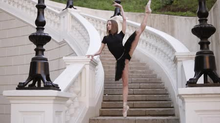 tüt : Slow motion of a young blonde girl in tutu standing on a beautiful white stairs outside on the street. Posing, practicing ballet movements Stok Video