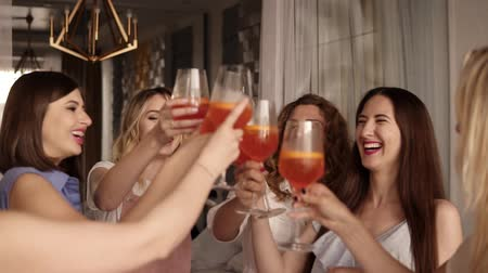 seis : Six beautiful stylish women in elegant casual outfit celebrating and drinking alcohol cocktails. Cheers. Beautiful, modern interior. Hen party. Slow motion