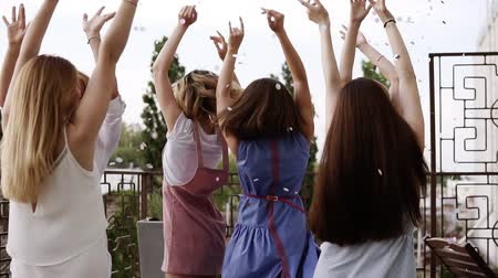 vzduch : Group of young girls dressed in casual partying outdoors on terrace silver confetti in the air at daytime during their carefree hen party. Dancing and hugging each other in circle. Slow motion Dostupné videozáznamy