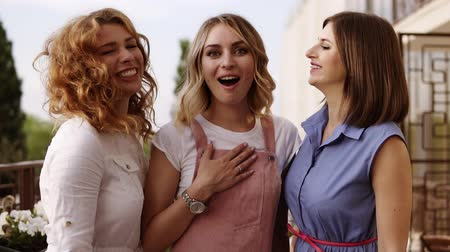 csók : The blonde girl is standing in the middle with excitement and her girlfriends kiss her on the cheeks. Hen party. Stylish women. Outside on a balcony. Front footage Stock mozgókép