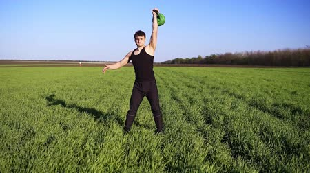 elevação : Front view of muscular young man engaged in lifting in the open area. Raises the weight with the left hand. The sun is shining Stock Footage