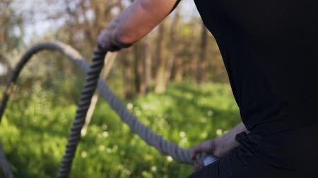 dayanıklılık : Aiming footage of a male arms waving battle ropes. Crossfit. Training. Spring time. Outdoor Stok Video