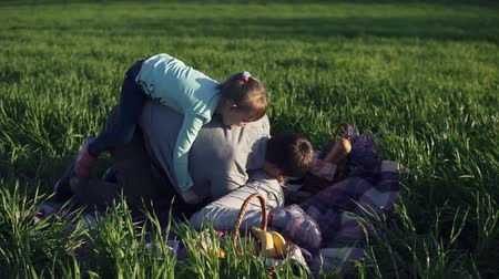 jumped : Wide meadow with green grass. Young father and two daughters are having fun together. Fool around. The youngest has jumped on the fathers back. Playing on the ground, on a picnic blanket