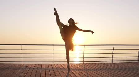 sznurek : Dancing ballerina in black ballet tutu and pointe on seafront above ocean or sea. Morning bosk. Young attractive woman practicing, making vertical twine, lunge forward in the dance