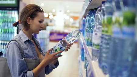 dönt : Shopping in store. Young pretty woman selecting bottle of water. Big assorment of water in the row, Side view Stock mozgókép