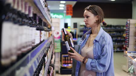 supermarket shelf : A woman in a supermarket in the alcohol department. Wine shelf. The girl chooses a bottle, holds a bottle of wine. Looks at prices