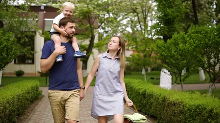 ártatlanság : Happy family walking on the street path together on a sunny day. Baby boy is riding on the fathers shoulders. Caucasian family. Front view Stock mozgókép