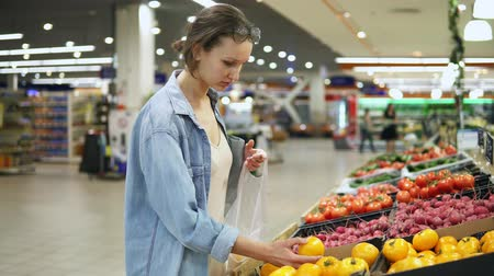 покупатель : Shopping. Woman choosing bio food yellow tomato in vegetable store or supermarket. Takes one by one and puts it in a cellophane bag. Yellow fresh tomatos