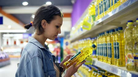 супермаркет : Girl in the store, reading information sticker on an oil bottle. Selected one bottle of sunflower oil, puts it n trolley. Assortment of products in the row