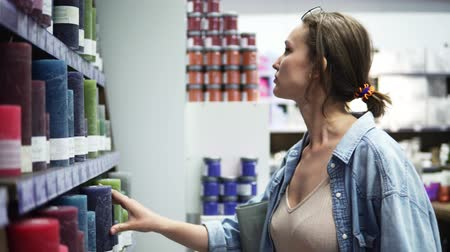 decidir : Side view of a young woman in denim shirt standing facing to shelves with assortment of candles. Holding candle in hands, thinkink, deciding Stock Footage