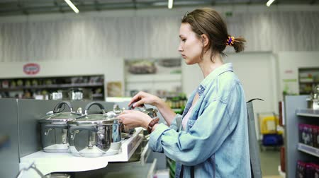 dolgok : A woman in a store in casual clothes. Standing near a shelf with pots, examines products. Selecting. Kitchen stuff. Housewife in supermarket. Side view