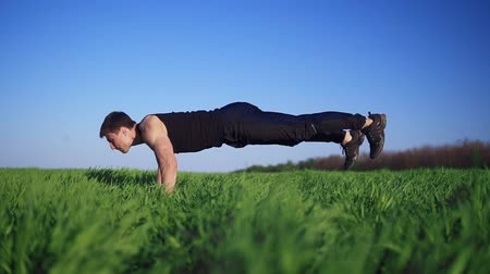 lökés : Young man doing push-ups with arms outstretched for a workout. Handsome White Caucasian. Green grass. Sunny day