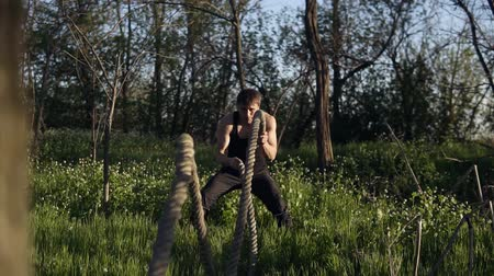 o : Young fit man practicing in the park. He uses crossfit ropes for training. Day time. Sun shines