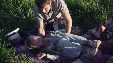 yalan : Pretty young man in park with his little children having fun. Playing with girls. They lie on the grass, laugh, their dad tickles them. Happy family time in nature Stok Video