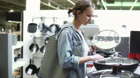 coisas : Handheld Footage of a young woman in denim shirt shopping. Looking for kitchen stuff. Examining various pots and pans with glass top. Supermarket, store. Side view