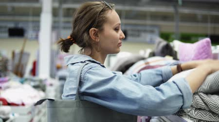 покупатель : A young positive fair-haired girl chooses pillows and a blanket on the racks in the store. Touches, checks the quality. Playfully take a nap on a pillow. Supermarket