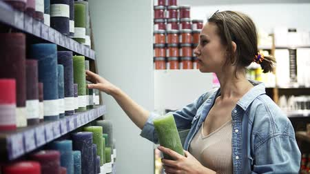 покупатель : Side view of an attractive woman choosing different colorful candles from the rack in supermarket. Smelling green candle from the shelf