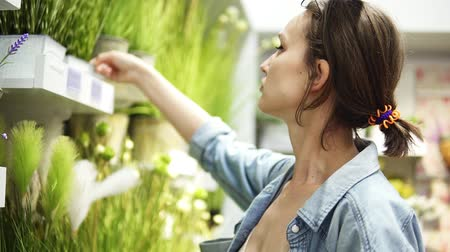 dönt : Pretty girl with fair hair looking on flowers from the store shelf. Flower in a white pot. Green grass. Positive, smiling person Stock mozgókép