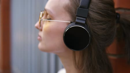 profil : Young Caucasian woman with black headphones outdoors on sunny summer day. Girl listening to music wearing yellow sungasses. Blurred motion. Side view Stock mozgókép