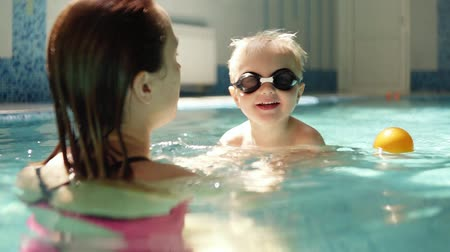basen : Young woman holding his son, teaching to swim. Supporting above the water. Indoors swimming pool. Little boy in swimming glasses