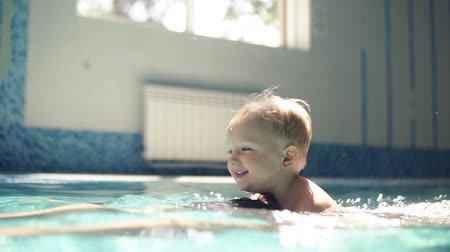 back side : Young man dives under the water. Rowing in the closed swimming pool. Little boy is onhis fathers back. Smilling. Mother is hugging them. Happy family time Stock Footage