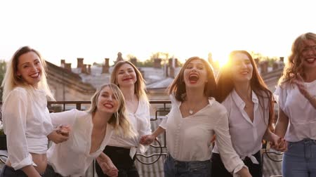 identical : Happy smiling outside on a balcony terrace. Building, city landscape background jumping together in slow motion. Having fun together, fashionable female in same clothes laughing. Enjoyment life
