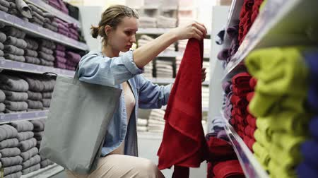 dönt : Caucasian woman choosing towels from big variety in the row. Shelves in store are fulled of different towels of any color. Girl unfolds one big red towel from the bottom shelf