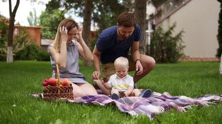 клетчатый : Happy family concept. Mother and son are sitting on plaid, enjoing picnic outdoors. Father brings some cones for his son. Picnic basket. Green park. Slow motion