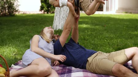 клетчатый : Young couple with a baby resting in the park on the grass. Happy family of three, with a baby, blonde haired boy. Beautiful parents mom and dad lying on a plaid. Dad is holding child with his hands