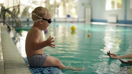 положить : A small swimmer prepares to swim. The boy sits on the edge of the pool, his mother puts on his glasses for swimming. Waving his feet on the water. Indoors Стоковые видеозаписи