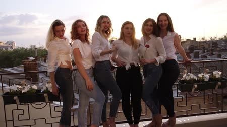podobný : Six caucasian girls are standing on a balcony and posing for the camera. Casual clothes. Close up of girls legs in jeans. Old city background