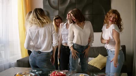tendo : Seductive, sexy young women on a hen party in identical casual clothes relaxed and dancing. Beautiful, modern interior. Slow motion