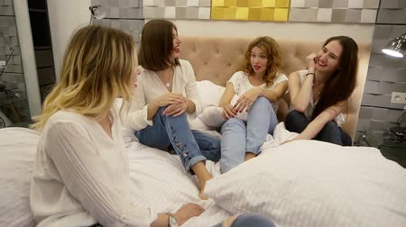 benzer : Close up footage of four girls sitting on a bed and chatting. Friendship. Beautiful modern room design. Fashionable women in similar clothes style