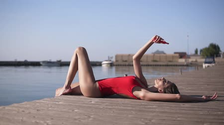 perfect weather : The girl lies on a wooden pier near the water and makes selfie on her cell phone. Seductive female model in a red swimsuit posing. Sunny, summer day Stock Footage