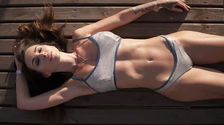 брюнет : Brunette sexy model lying on a wooden pier near the water in silver swimming suit. Beautiful, perfect body. Footage from above