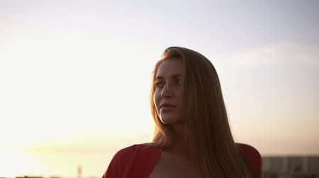 zábradlí : Footage from above of a young, blonde haired woman standing near the sea or ocean in morning dusk. Wearing red swimsuit and red gown. Perfect fit body Dostupné videozáznamy