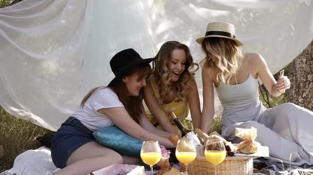 pléd : Front footage of three young attractive girls playing card game. Picnic, bachelorette concept. Outdoors, white cloth on the background