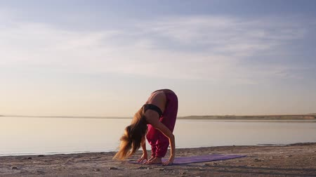sakk : Flexible healthy young girl practice yoga beach. Stretching. Sealine sunrise slow motion Stock mozgókép