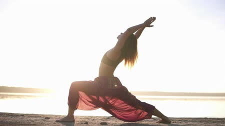 hatha : Side view of attractive young woman practicing yoga in warrior pose Virabhadrasana on seashore. Light sun haze