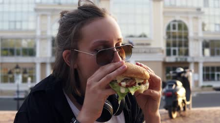 faminto : Young female eats a big, juicy hamburger with two hands. Young girl with short hair and dark sunglasses. Hungry. Close up