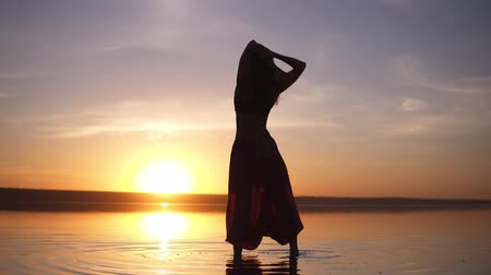 longhair : Silhouette of a slender girl walking on the water in yoga pants, raises her hands. Carefree, freedom. Incredible sunset in the background