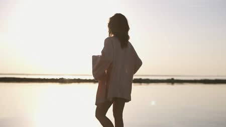 cüppe : Shooting in the morning haze a girl walks in a light gown and a swimsuit along the sea. Beautiful brunette in morning dusk and sunlight posing in swimming suit Stok Video
