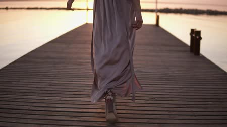sexy heels : Tall, slender female model walking by the wooden pier on the sea. Woman walking straight in bright, silk dress and heels. Backside view. Tracking footage Stock Footage