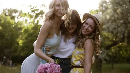hippi : Three beautiful women posing for the camera. Hugging, smiling. Bachelorette concept. Girls having fun together in the green park