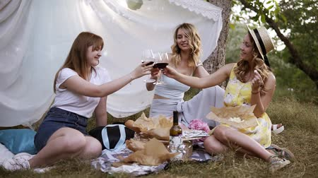 ヒッピー : Hen party outdoors. Three pretty woman have a picnic, sitting on the plaid, drinking red wine. Cheers. White sheet hanging on a trees